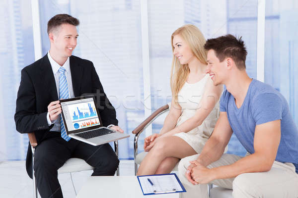 Financial Advisor Showing Graph On Laptop To Couple Stock photo © AndreyPopov