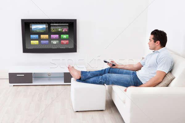 Man Applying Settings On Television Stock photo © AndreyPopov
