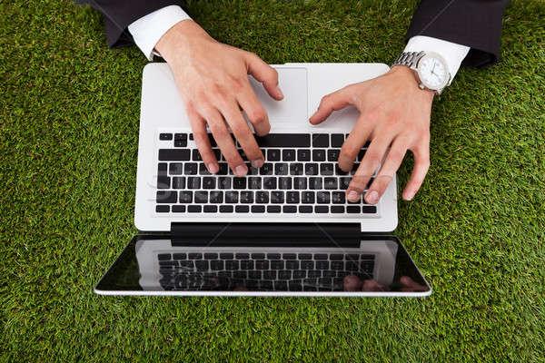 Empresário usando laptop grama diretamente acima tiro Foto stock © AndreyPopov