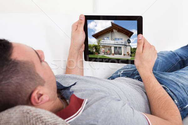 Young man selecting new house on digital tablet Stock photo © AndreyPopov