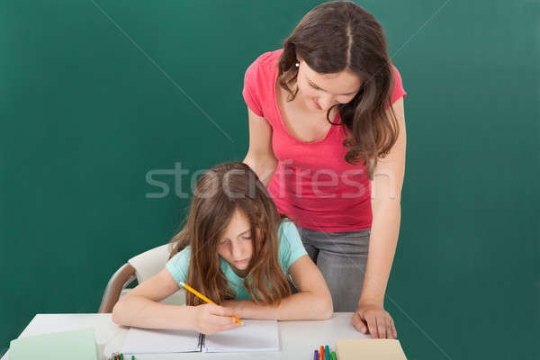 Teacher Assisting Girl In Studying Stock photo © AndreyPopov