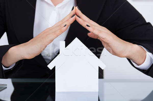 Businesswoman Covering House Model Stock photo © AndreyPopov