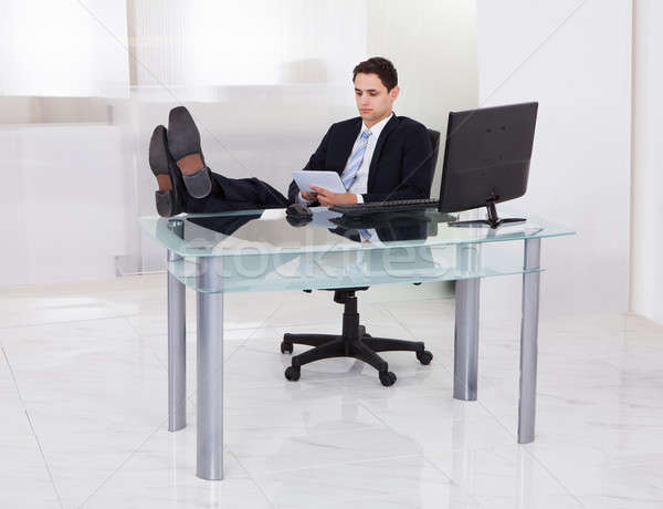 Relaxed Businessman Using Digital Tablet In Office Stock photo © AndreyPopov