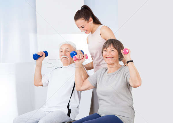 Trainer Assisting Senior Couple With Dumbbells Stock photo © AndreyPopov