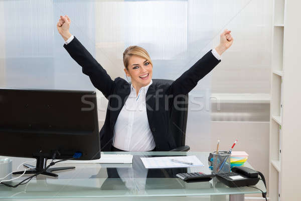 Businesswoman Raising Hands In Office Stock photo © AndreyPopov