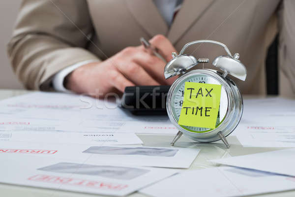 Businessman With Tax Time Reminder Note On Alarm Clock Stock photo © AndreyPopov