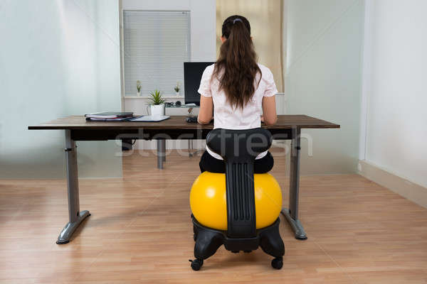 Businesswoman Sitting On Fitness Ball In Office Stock photo © AndreyPopov