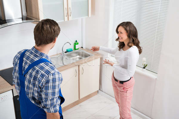 Woman Showing Damage In Sink To Plumber Stock photo © AndreyPopov