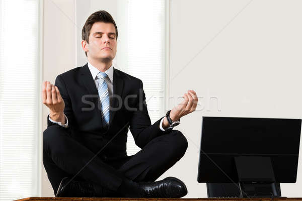 Businessman Sitting In Lotus Position At Desk Stock photo © AndreyPopov