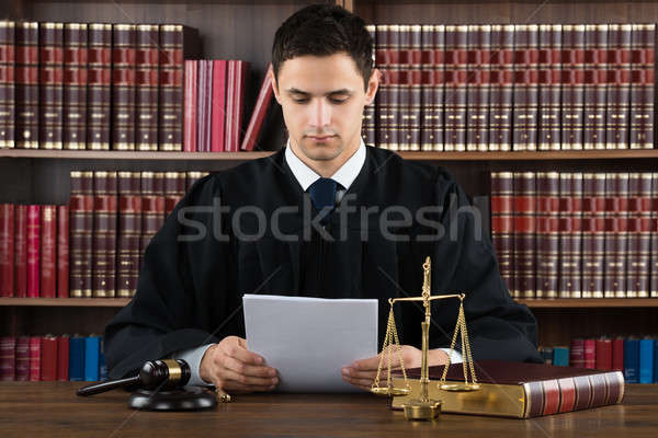 Stock photo: Judge Reading Documents At Desk In Courtroom