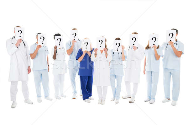 Medical Team Covering Faces With Question Mark Signs Stock photo © AndreyPopov