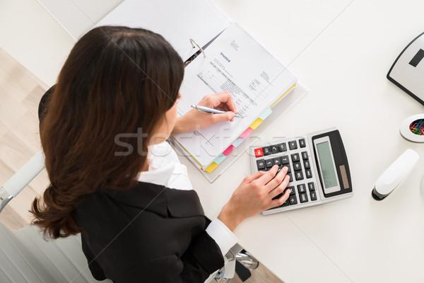 Empresária financeiro cálculo secretária diretamente acima Foto stock © AndreyPopov