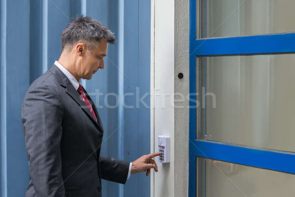 Businessman Using Door Security System On Wall Stock photo © AndreyPopov