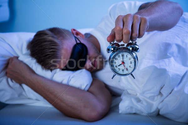 Hombre dormir despertador mano cama Foto stock © AndreyPopov