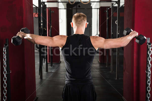 Man Getting Trained With Dumbbell Stock photo © AndreyPopov