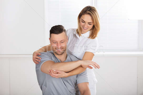 Smiling Female Physiotherapist Giving Shoulder Exercise Stock photo © AndreyPopov