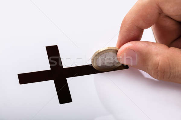 Hand Inserting Coin In Crucifix Slot Stock photo © AndreyPopov