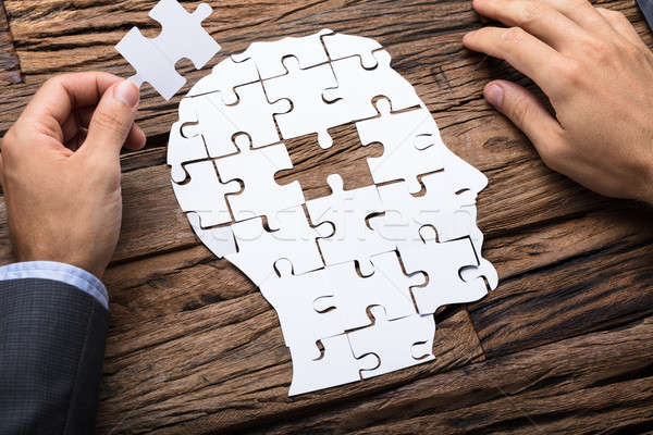Businessman Holding Paper Jigsaw Puzzle Piece While Making Head Stock photo © AndreyPopov