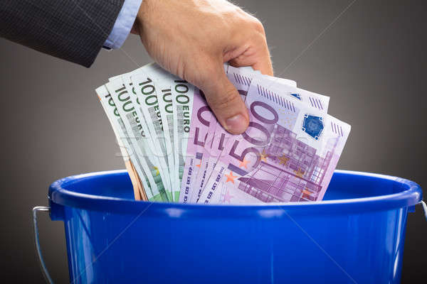 Businessman's Hand Throwing Euro Notes In Blue Bucket Stock photo © AndreyPopov