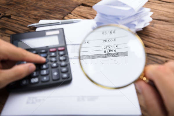 Businessman Examining Invoice With Magnifying Glass At Table Stock photo © AndreyPopov