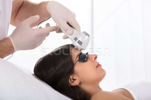 Woman Getting A Laser Treatment On Forehead Stock photo © AndreyPopov