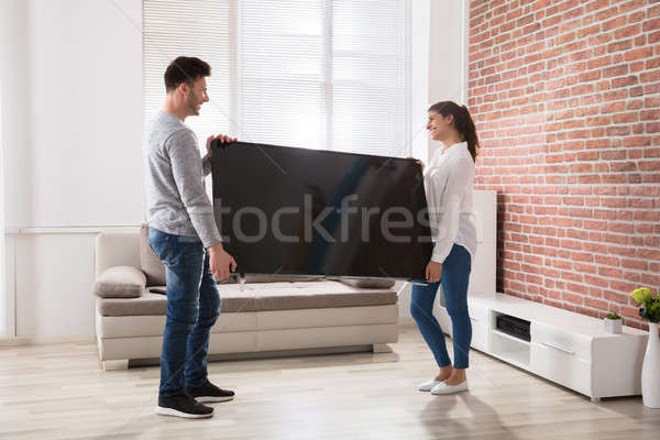 Сток-фото: пару · телевидение · домой · улыбаясь