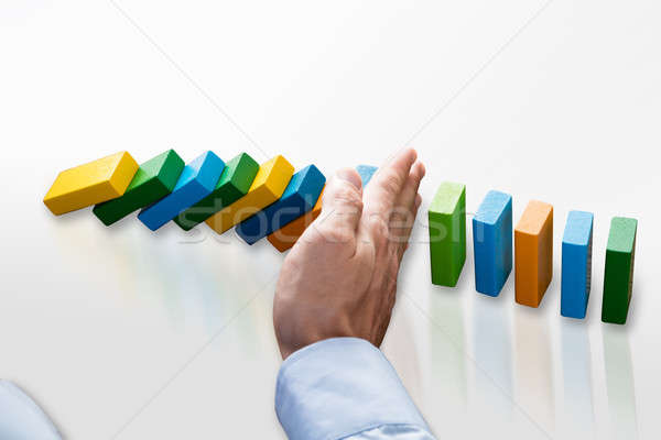 Businessperson Stopping Falling Dominoes Stock photo © AndreyPopov