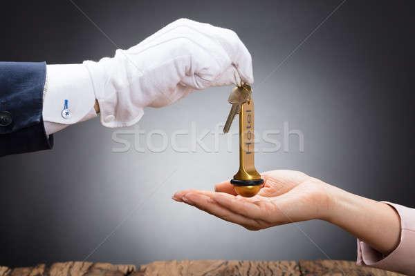Receptionist Giving Hotel Door Key To Customer Stock photo © AndreyPopov