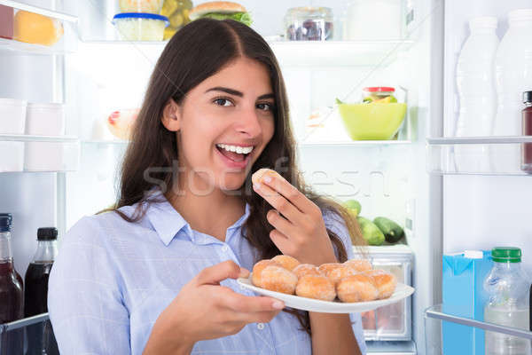 Smiling Woman Eating Cookies In Plate Stock photo © AndreyPopov