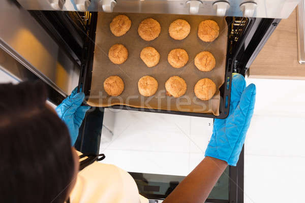 Human Hand Taking Out Tray Of Baked Cookies From Oven Stock photo © AndreyPopov