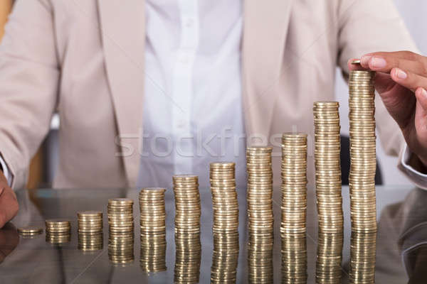 Businesswoman Hand Placing A Coin On Increasing Coin Stacks Stock photo © AndreyPopov