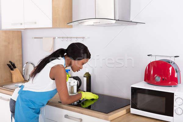 Háziasszony takarítás tűzhely fiatal afrikai konyha Stock fotó © AndreyPopov