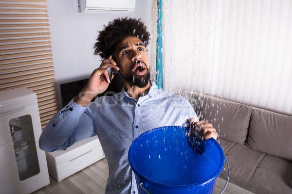 Man Calling Plumber While Leakage Water Falling Into Bucket Stock photo © AndreyPopov