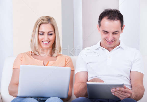 Mid-adult Couple Using Laptop And Digital Tablet Stock photo © AndreyPopov