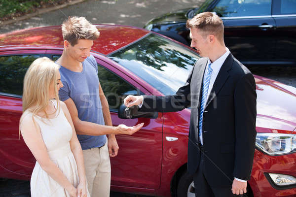 Stock photo: Salesman Giving Key To Couple By Car