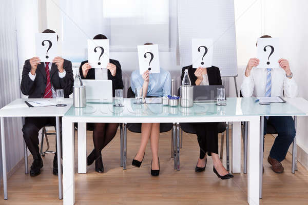 Businesspeople Holding Question Mark In Front Of Face Stock photo © AndreyPopov