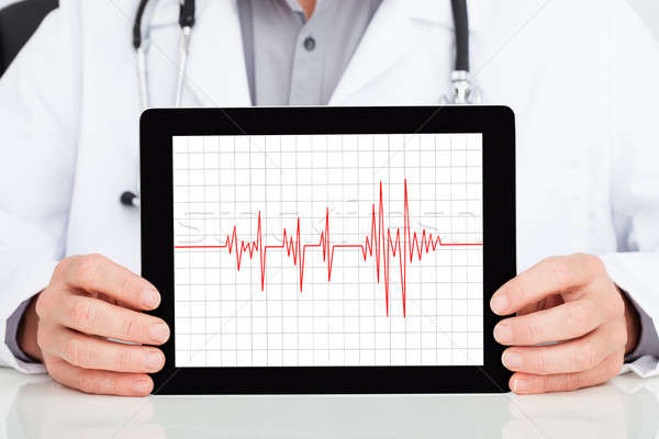 Doctor Showing Heartbeat On Digital Tablet Stock photo © AndreyPopov