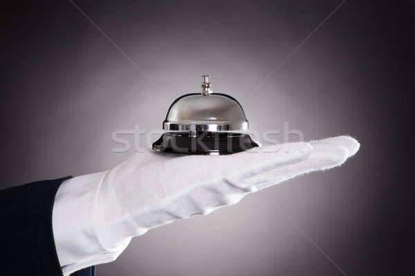 Cropped Image Of Bellman Holding Bell Stock photo © AndreyPopov