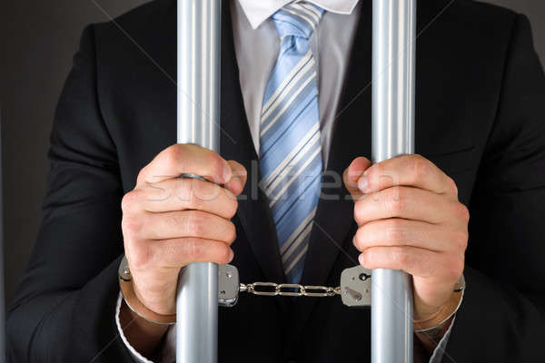 Handcuffed Businessman Holding Bars Stock photo © AndreyPopov