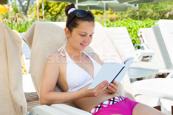 Woman Reading Book On Lounge Chair At Resort Stock photo © AndreyPopov