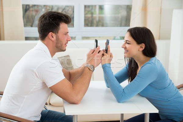 Happy Couple Holding Cellphones Stock photo © AndreyPopov