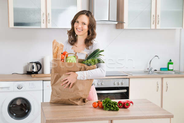 Woman With Grocery Bag In Kitchen Stock photo © AndreyPopov