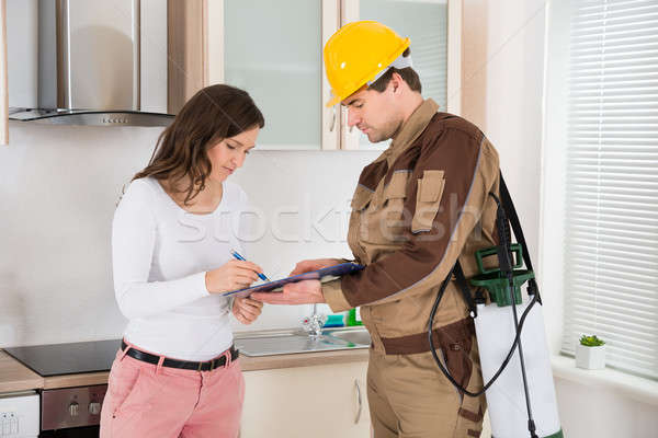 Woman Signing Document In Front Of Exterminator Stock photo © AndreyPopov