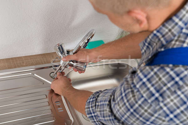 Plumber Fixing Faucet In Kitchen Sink Stock photo © AndreyPopov
