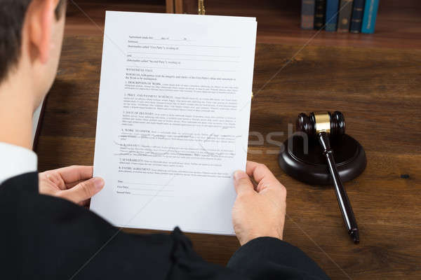 Stock photo: Judge Reading Legal Documents At Desk In Courtroom