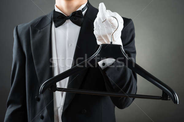 Midsection Of Male Housekeeper Holding Hanger Stock photo © AndreyPopov