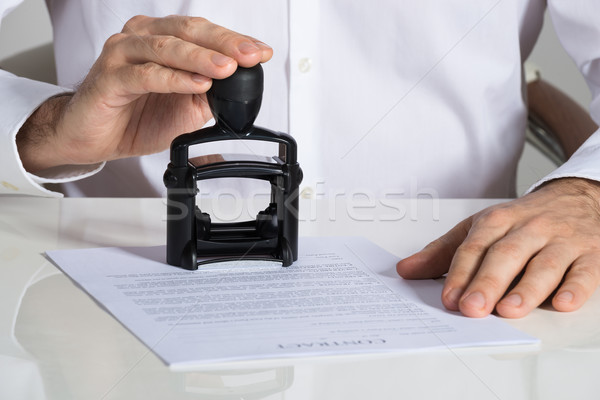 Businessman Stamping Contract Document Stock photo © AndreyPopov