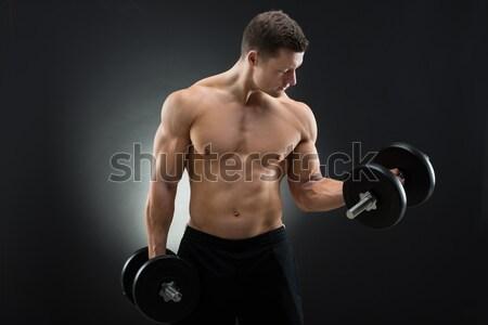 Determinado muscular hombre pesas negro Foto stock © AndreyPopov