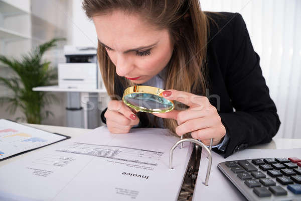 Businesswoman Examining Invoice With Magnifying Glass Stock photo © AndreyPopov