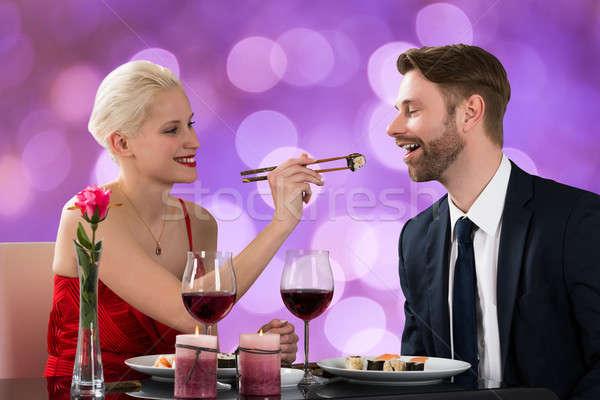 Woman Feeding Man At Restaurant Table Stock photo © AndreyPopov